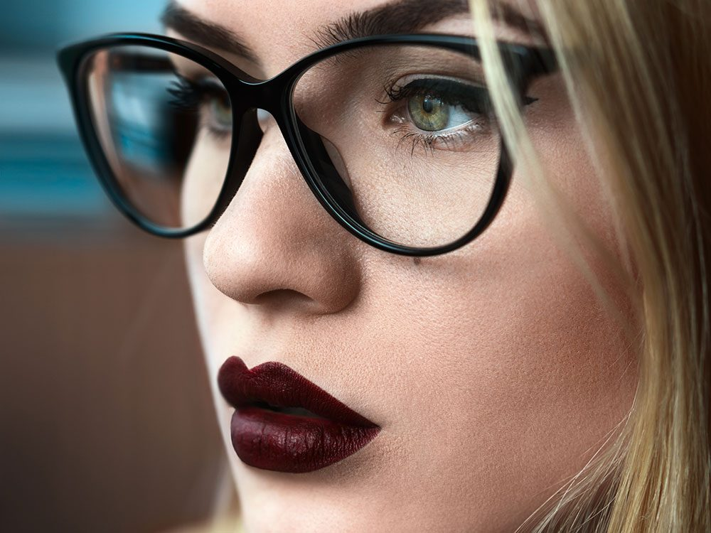 Woman with dark lip and dark framed glasses
