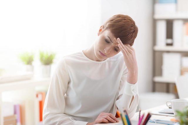 Woman having a headache at work