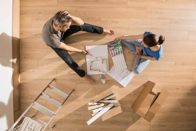 Young couple planning on living room floor