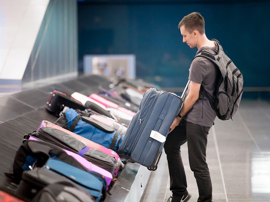Man picking up checked bags