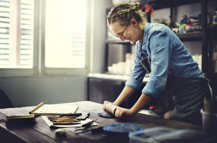 Woman rolling clay