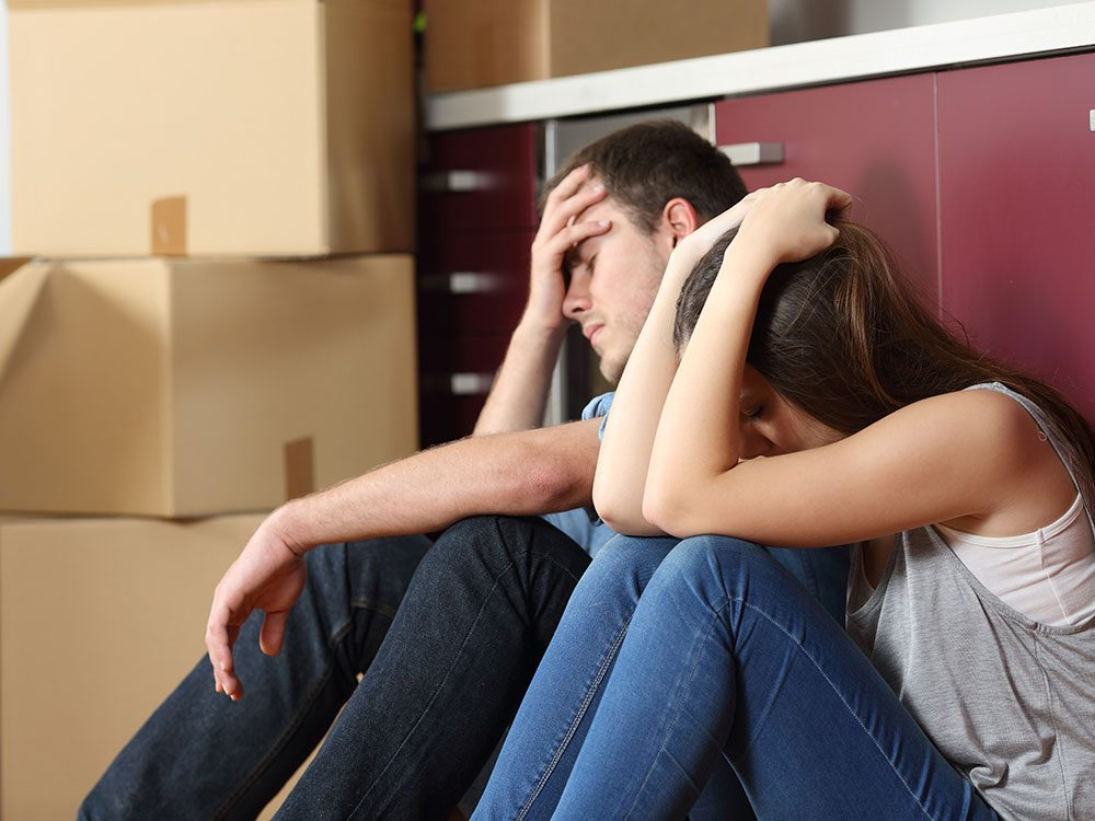 Young frustrated couple moving in to rental apartment