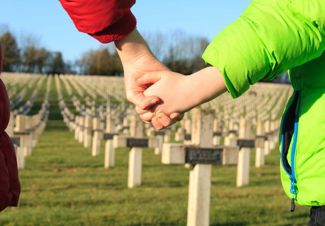 Mother and child at cemetery during Remembrance Day