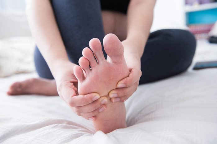 Woman in bed with sore toe