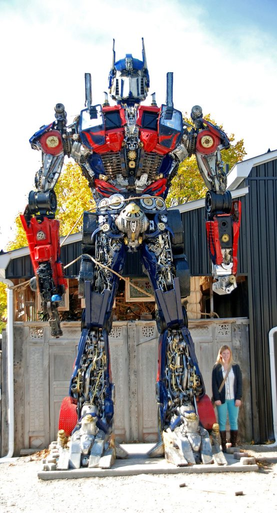 Woman standing next to Transformers replica