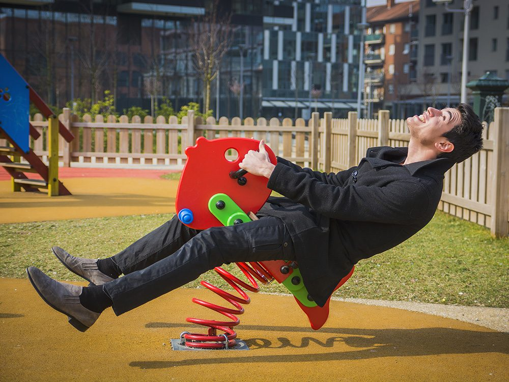 Adult man acting like a child at playground