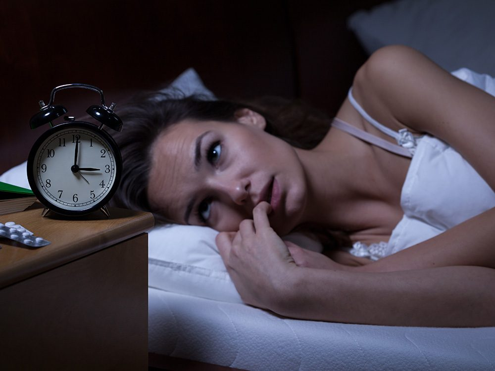 Woman in bed trying to avoid the Sunday night blues