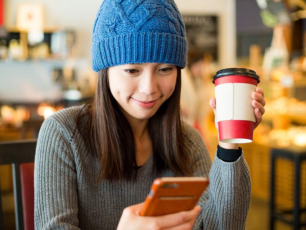 Woman looking at her phone at coffee shop