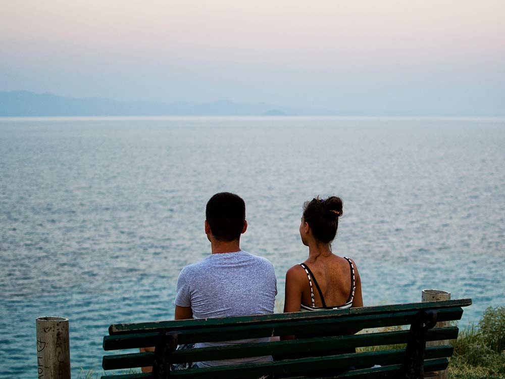 Couple on bench watching the ocean