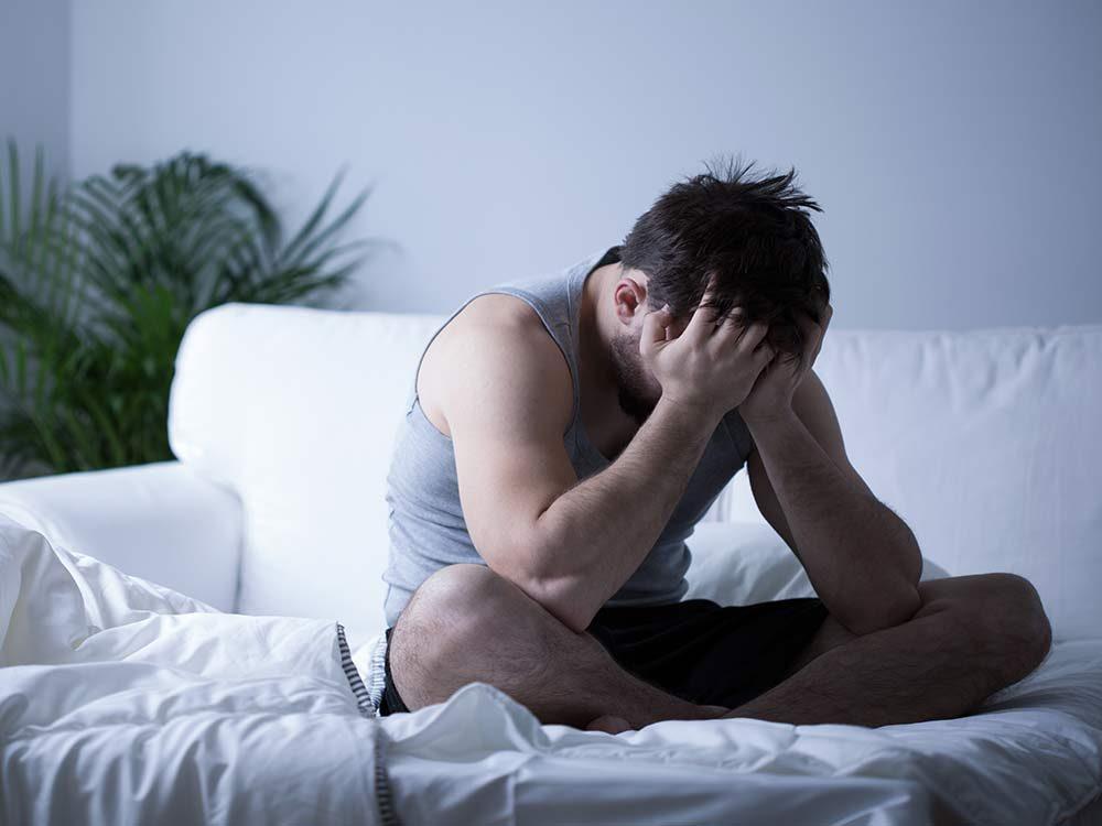 Depressed man on bed
