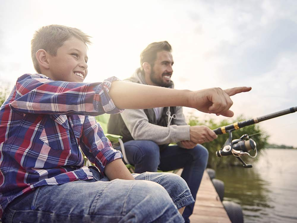Father and young son fishing on dock