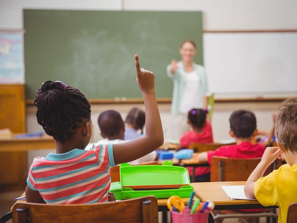 Young girl raising her hand in classroom