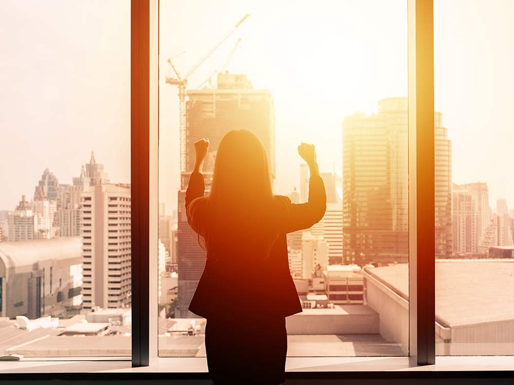 Businesswoman with arms up by office window
