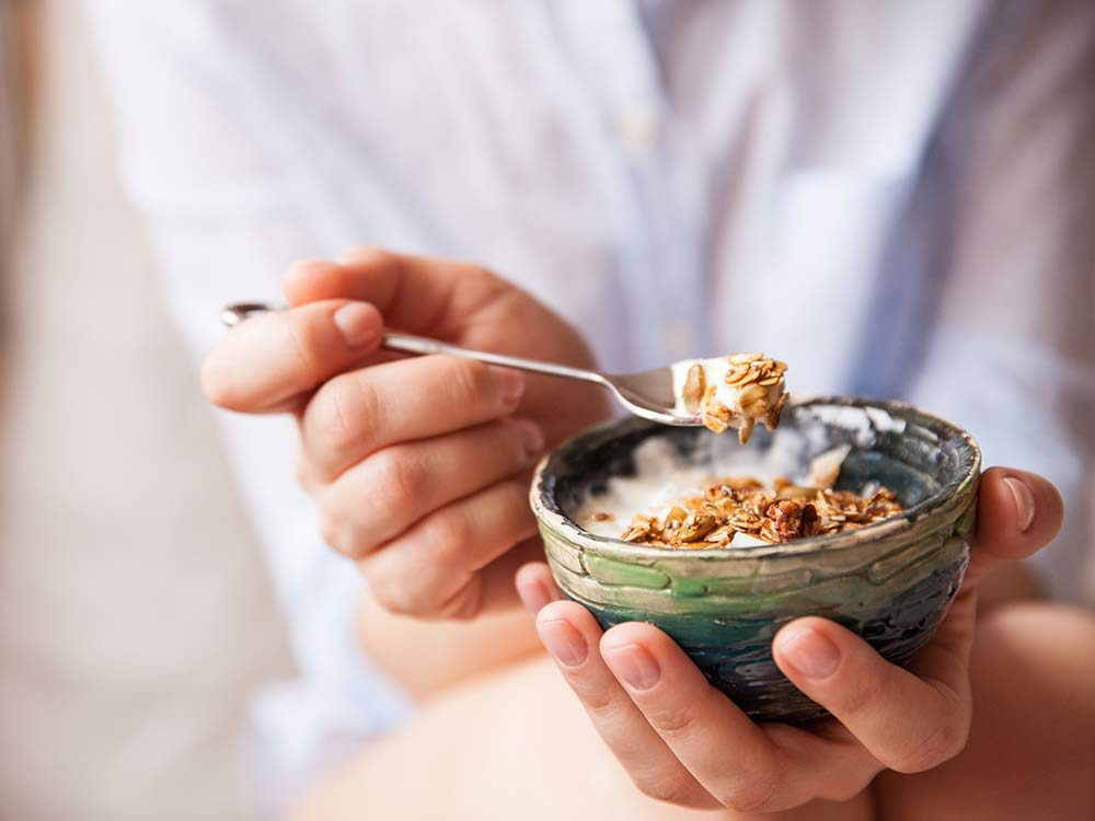 Woman eating small cereal bowl