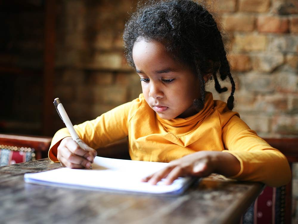 Child writing in her notebook