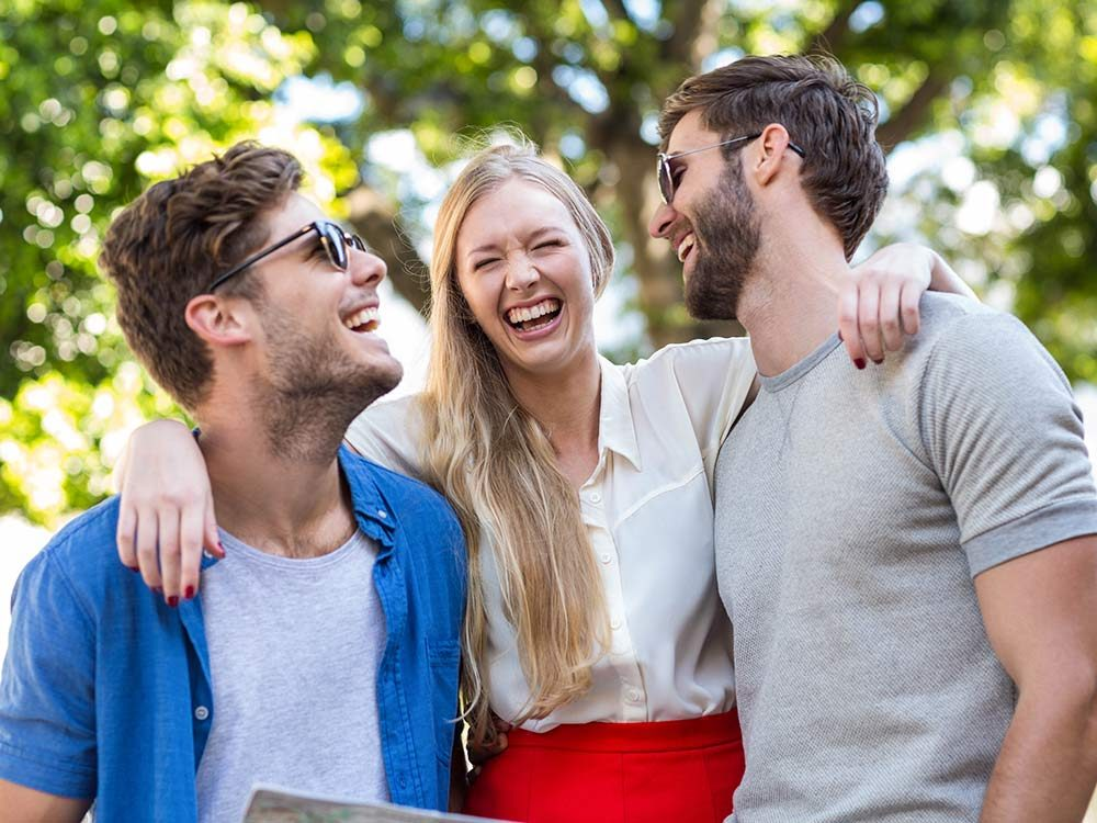 Three hip young friends laughing outside