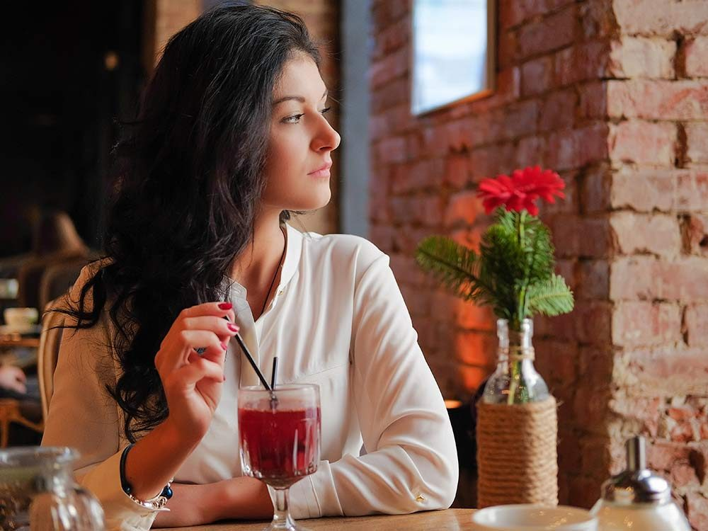 Woman drinking mulled wine alone at restaurant