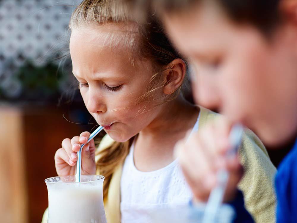Siblings drinking milkshakes at cafe