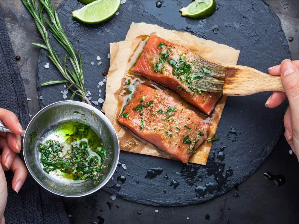 Applying marinade onto salmon steaks