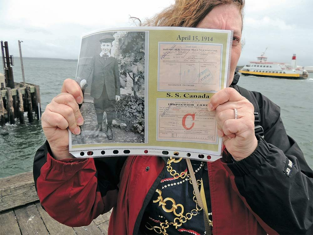 Janey in Portland, Maine, holding a photo of her dad, along with his 1914 boarding pass