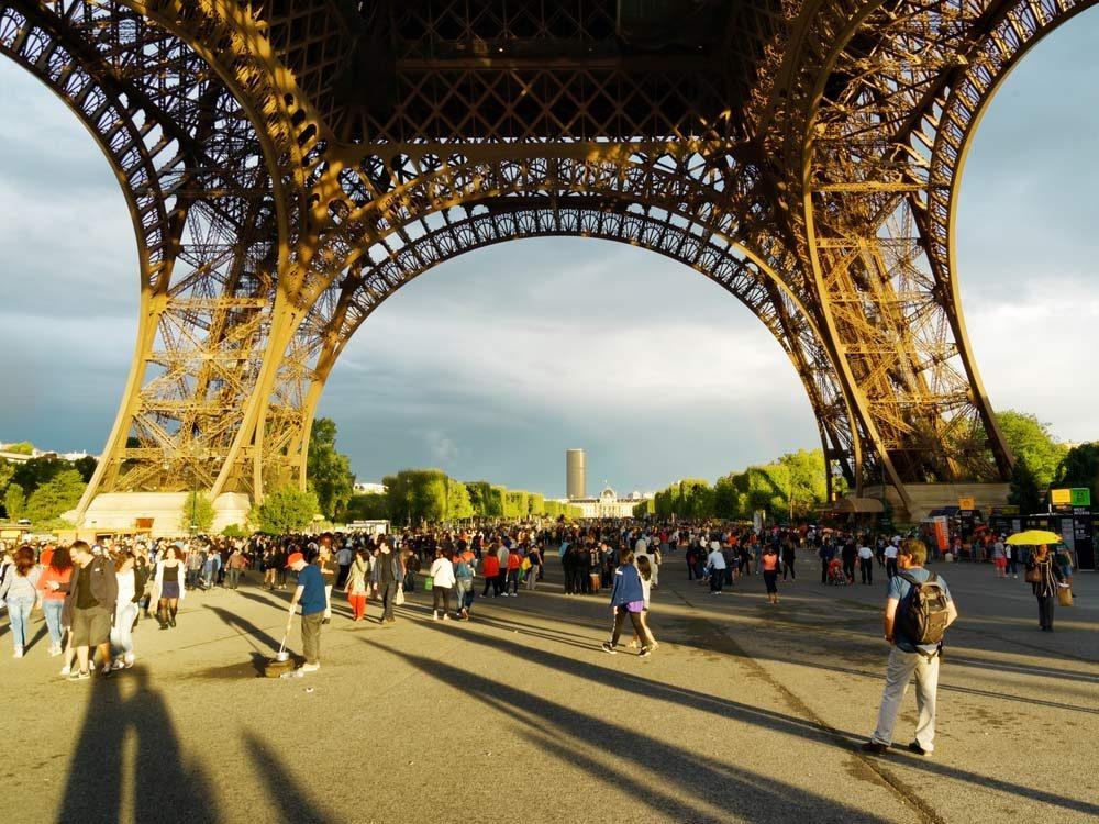 Tourists walking under the Eiffel Tower
