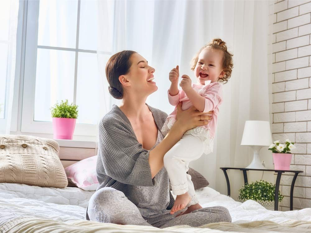 Mother and young daughter laughing and playing