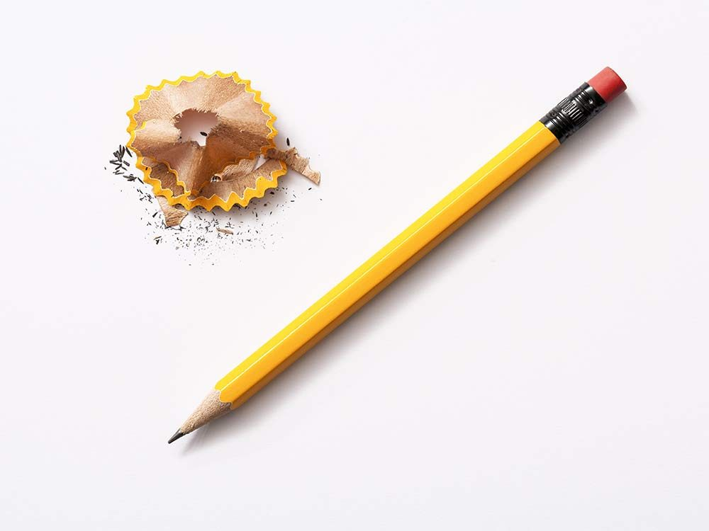 Yellow pencil with pencil shavings on white background