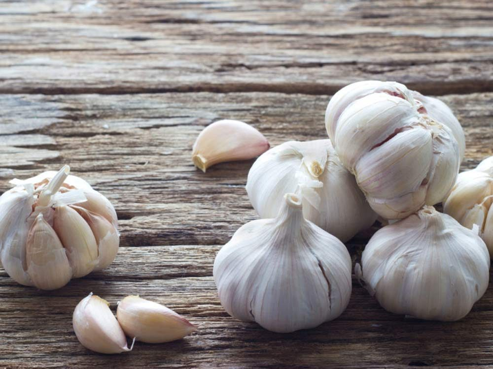 Garlic head and cloves on wooden table