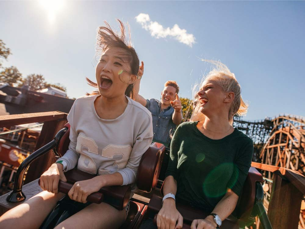 Two female friends riding roller coaster