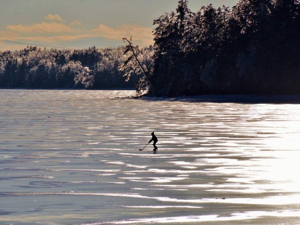 Little boy playing hockey himself on frozen river in Miramichi, New Brunswick