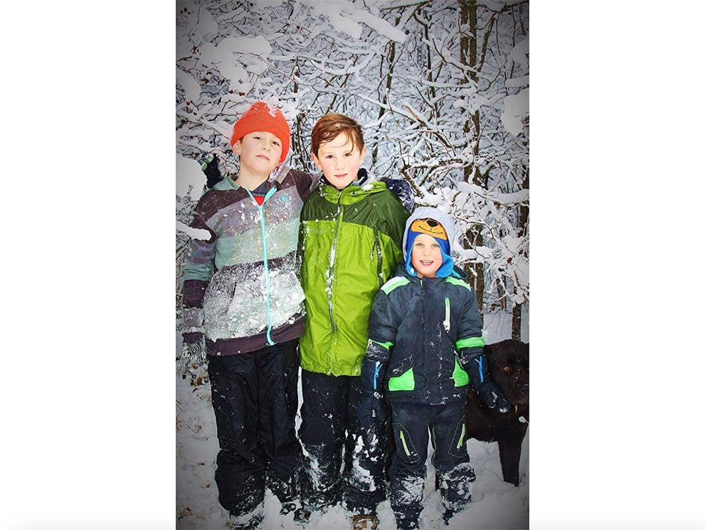 Three young boys posing for photo next to River Bank in Laurier, Manitoba