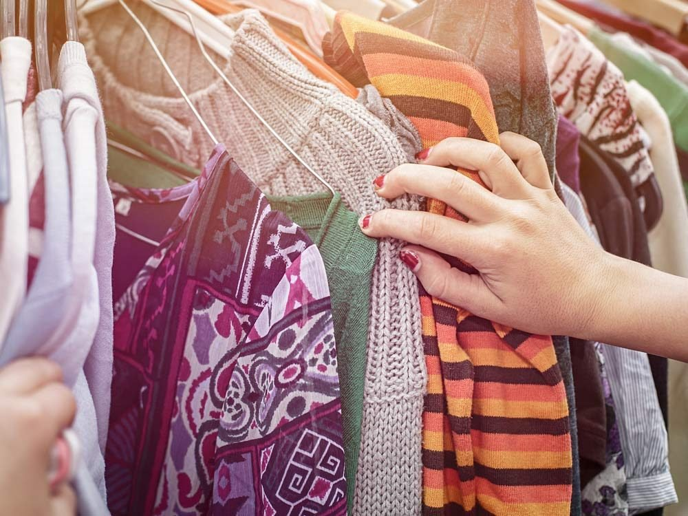 Woman looking through clothes at garage sale