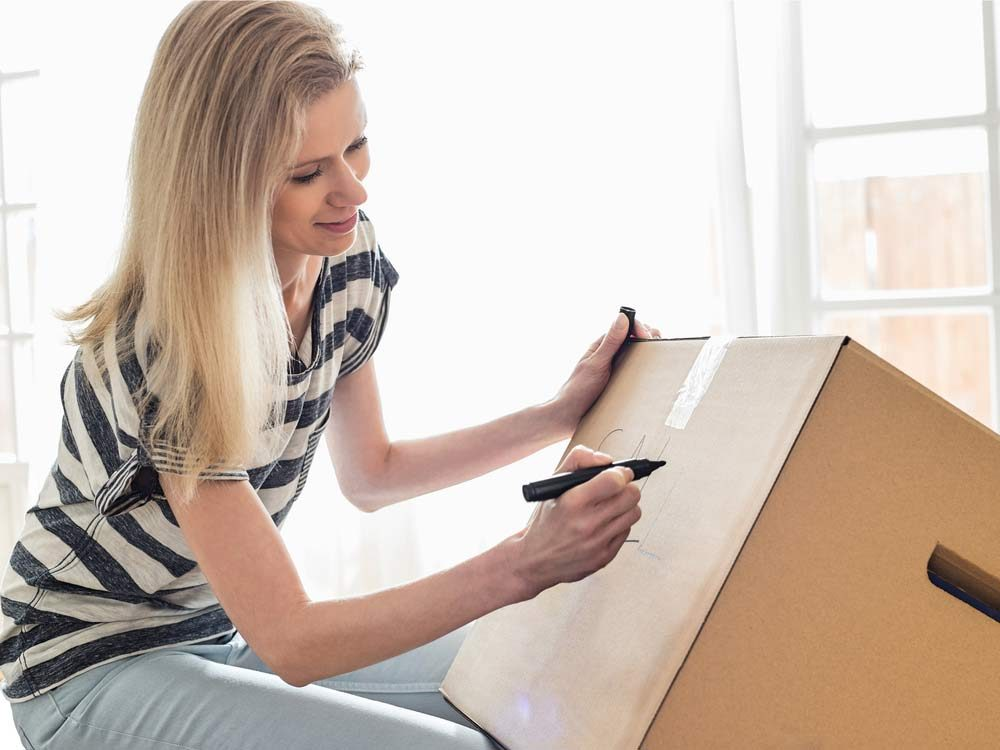 Woman labelling box on moving day