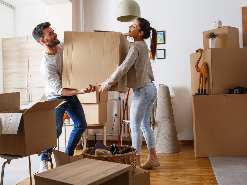 Couple carrying heavy cardboard box on moving day