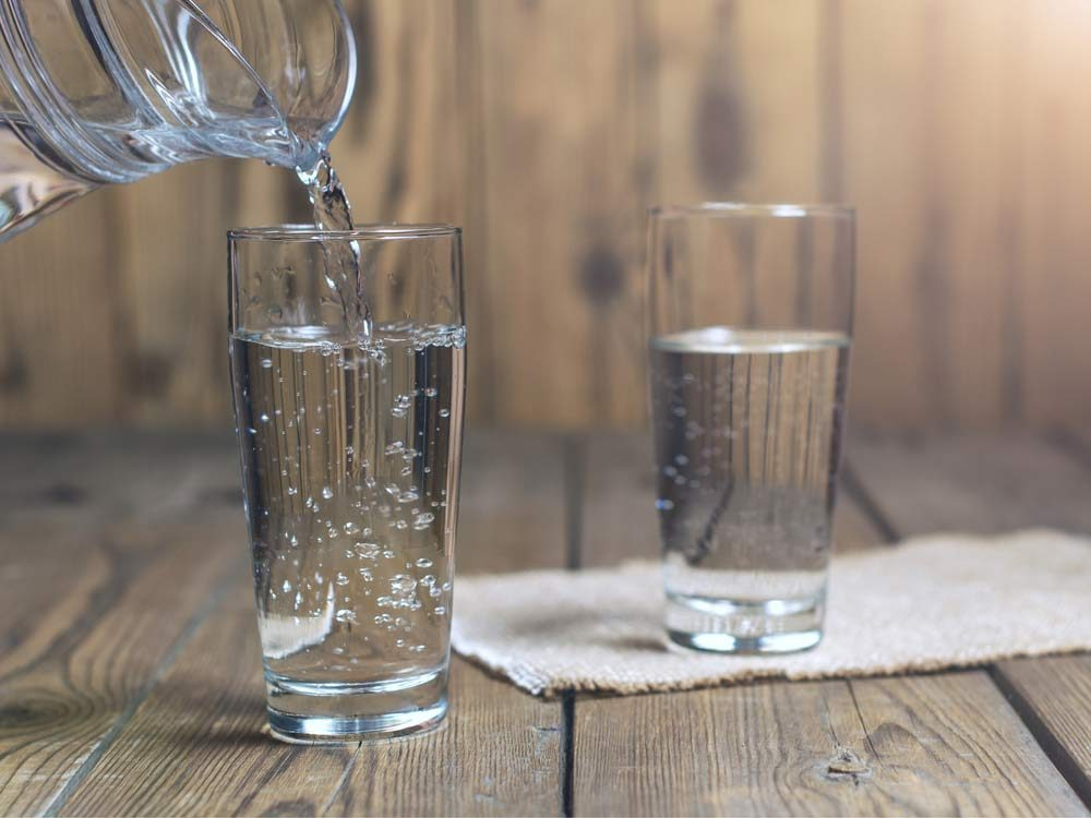 Water being poured into clear glasses