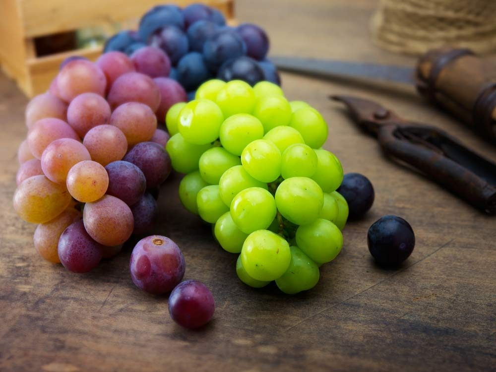 Purple and green grapes on wooden table