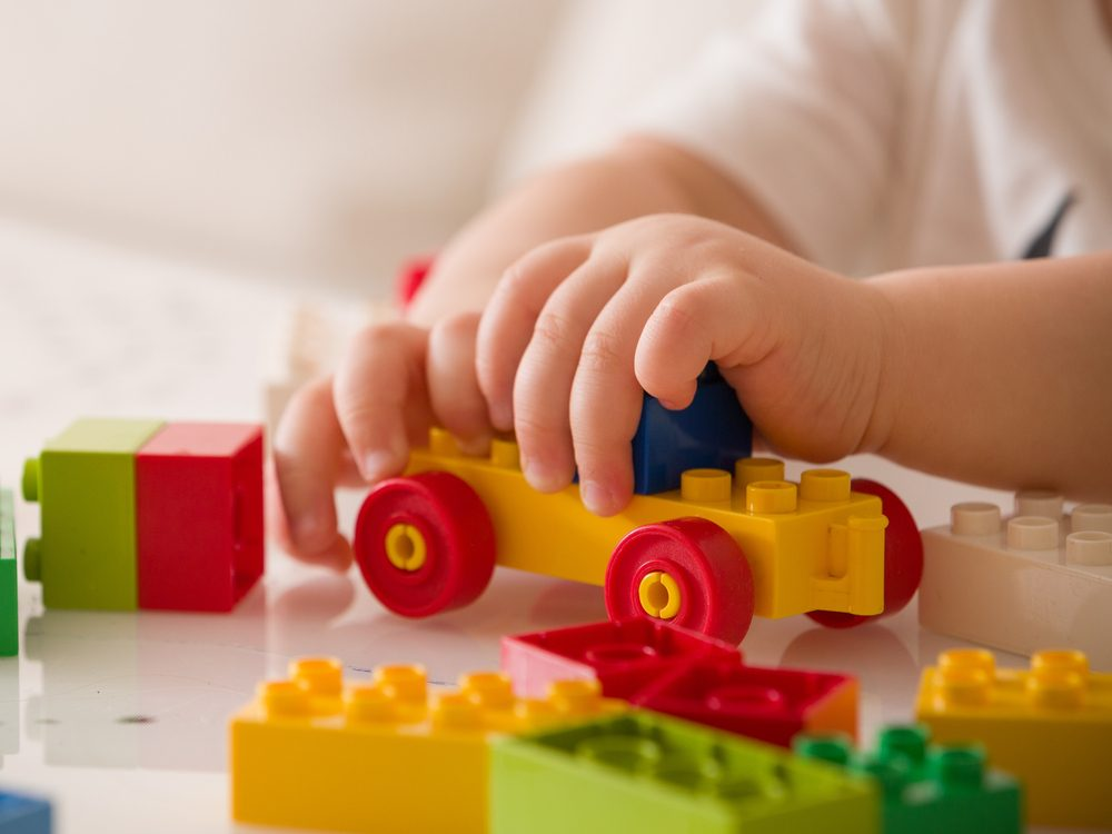 Close up of child's hands playing with colorful plastic bricks at the table