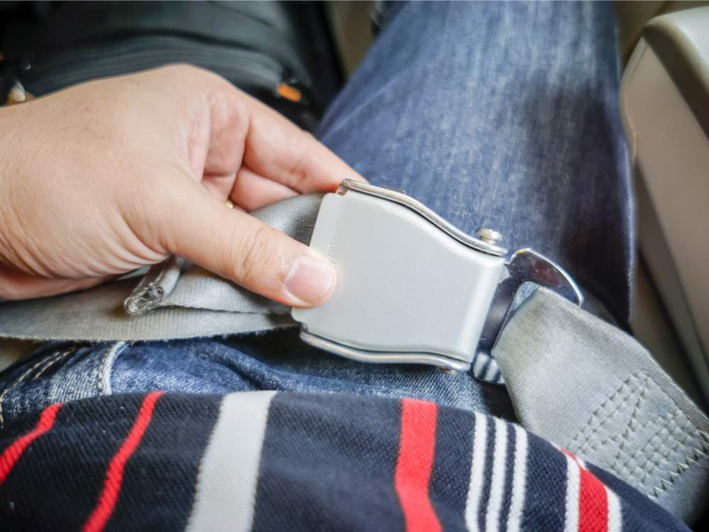 Female passenger adjusting seatbelt on airplane
