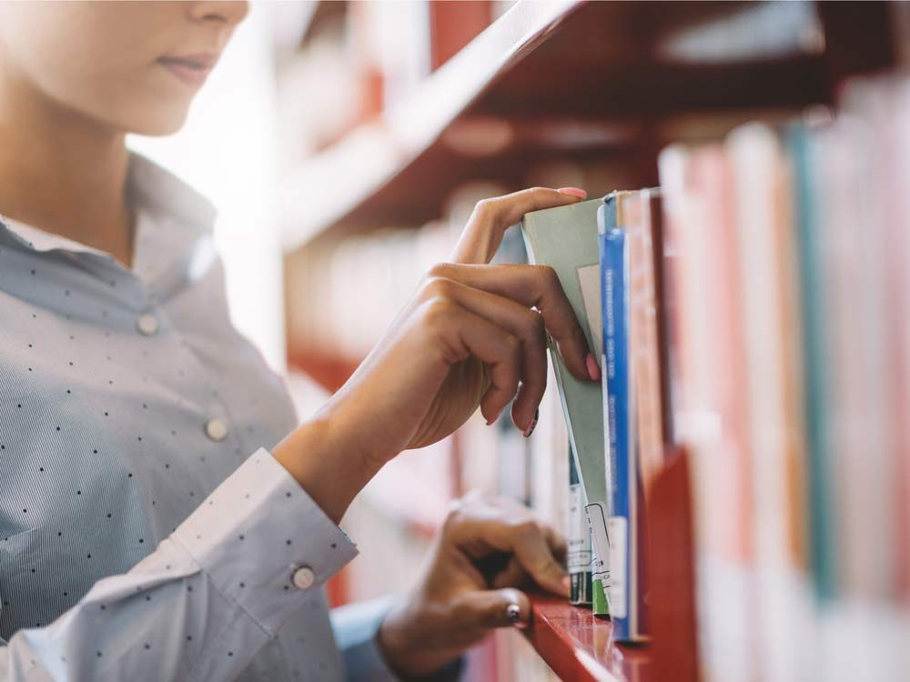 Woman looking through books at public library