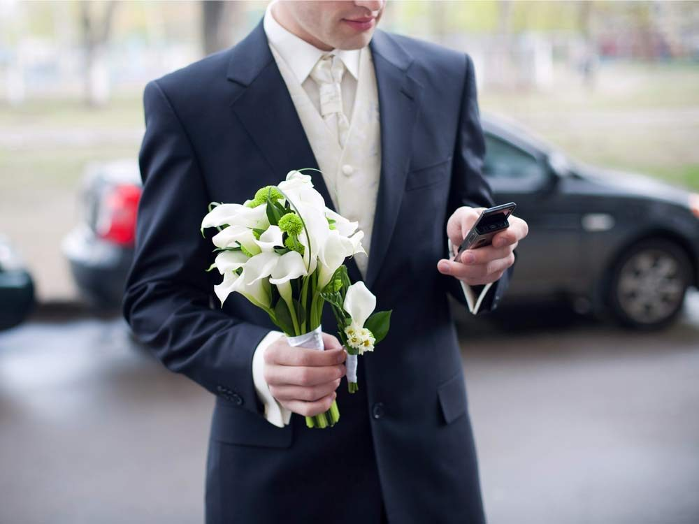 Groom using phone during ceremony