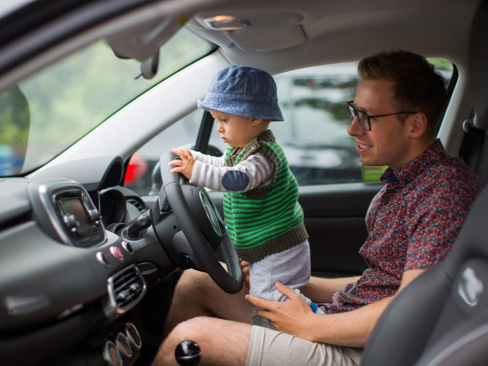 Father driving with toddler