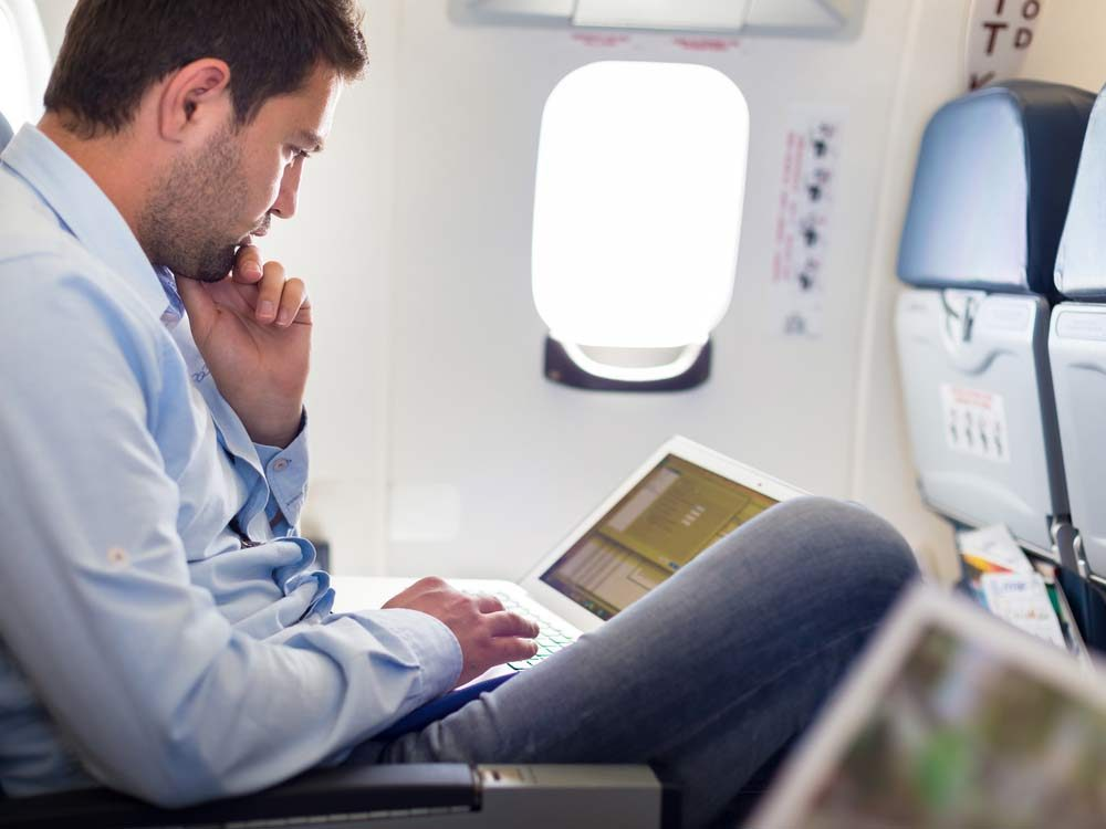 Man using laptop on plane