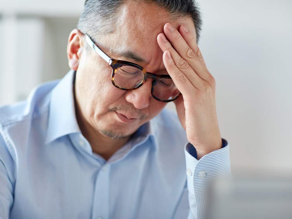 Asian man experiencing severe headache