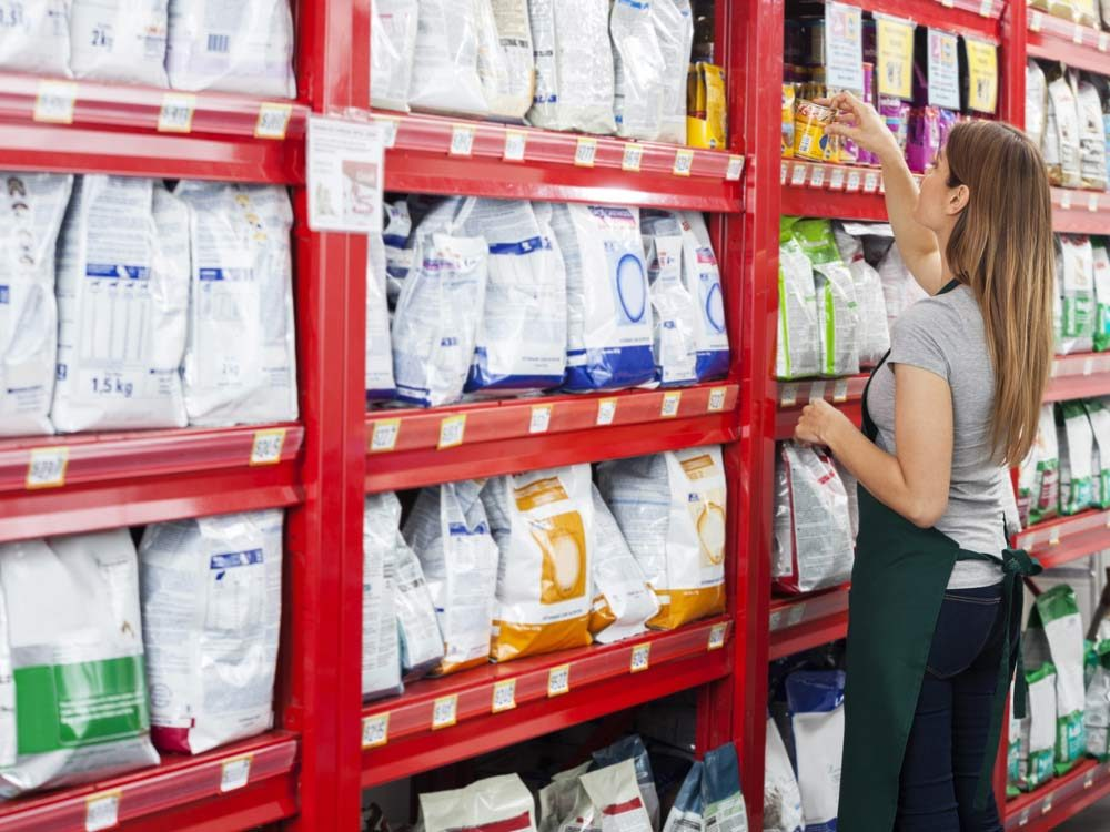 Pet store employee organizing pet food bags
