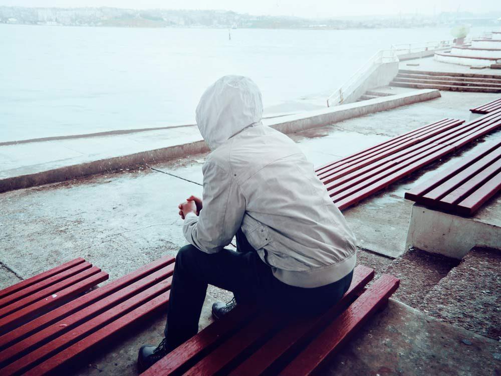 Young man sitting on promenade
