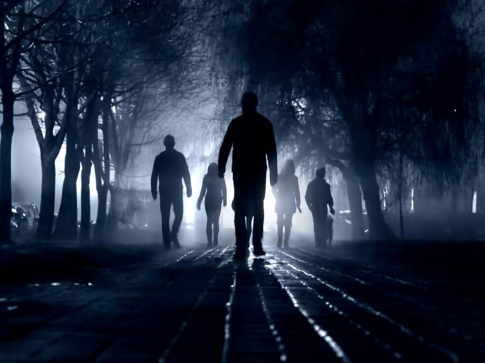 Silhouette of zombies walking at night