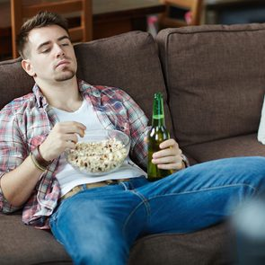 Signs you need to exercise more - man watching TV on couch