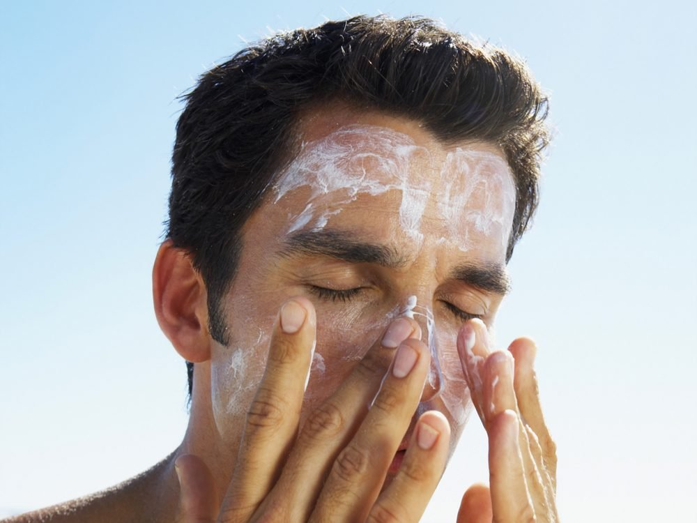 Man applying sunscreen on beach