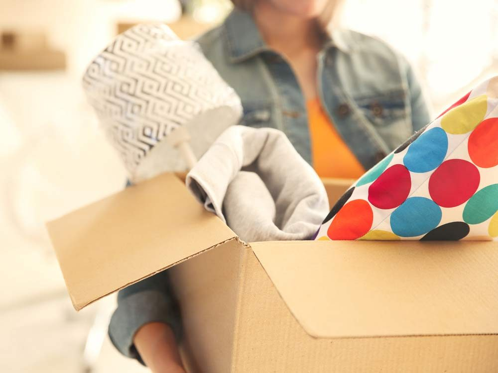 Young woman holding cardboard box of objects
