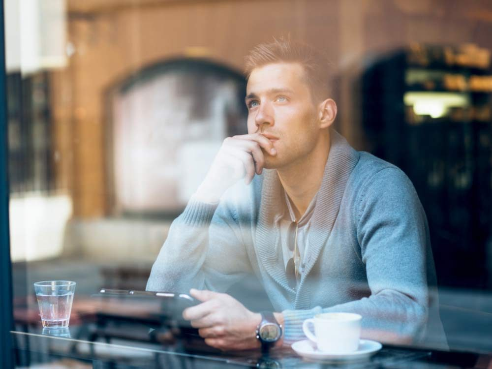 Young man thinking while sitting in coffee shop